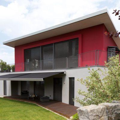 Raffstoren an einem roten Haus
